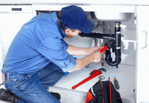 A man fixing kitchen sink pipes